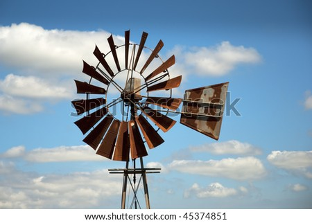 Rusty windmill with clouds in the background - stock photo