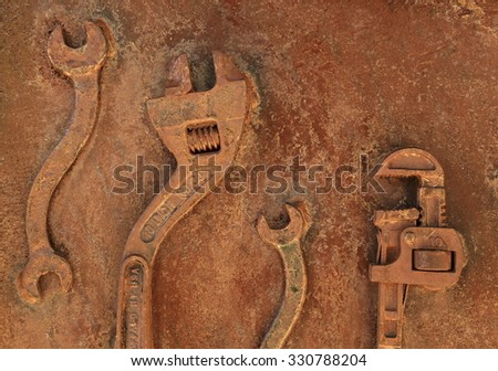 Rusty work tools on a rusty wall - stock photo