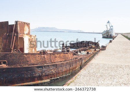 Rusty wreck moored, abandoned in the pier in the harbor of Cagliari Sardinia. - stock photo
