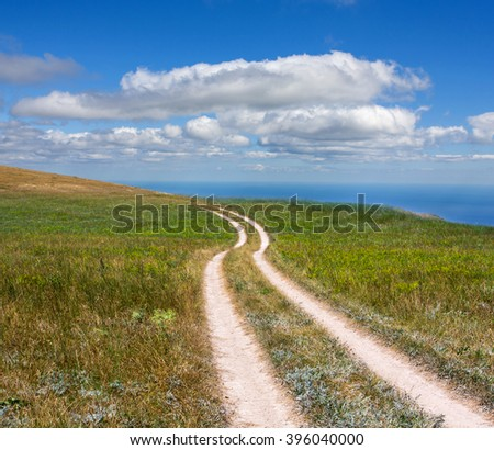 rut road across meadow under nice clouds in sky - stock photo