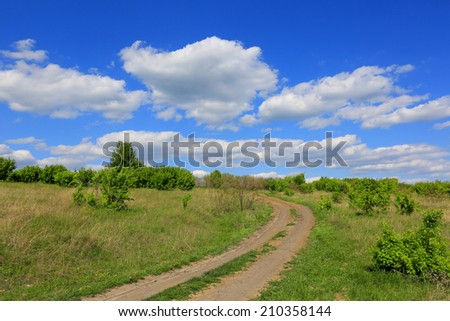 rut rural road over meadow in steppe - stock photo