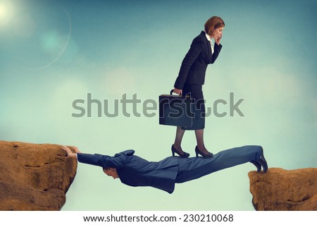 ruthless business woman walking over a rival businessman - stock photo