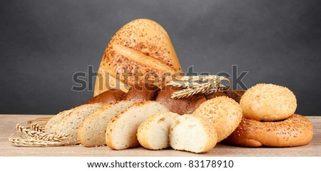 rye and white bread and buns on wooden table on gray background