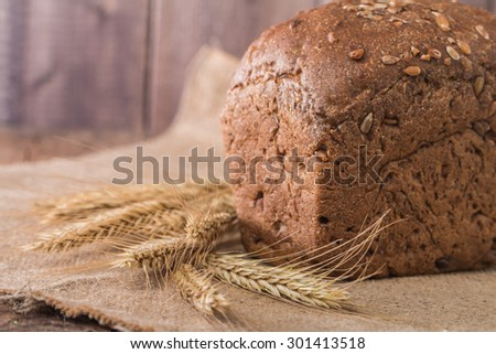 rye Bread and spikelets on wooden background - stock photo
