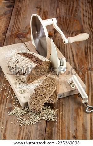 Rye bread on old cutting board / slicer  on wooden background