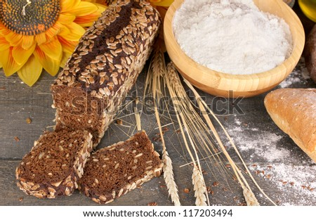 Rye bread on wooden table on wooden background close-up - stock photo
