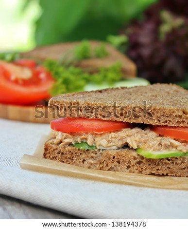 Rye bread sandwich with tuna fish, tomato and cucumber slices