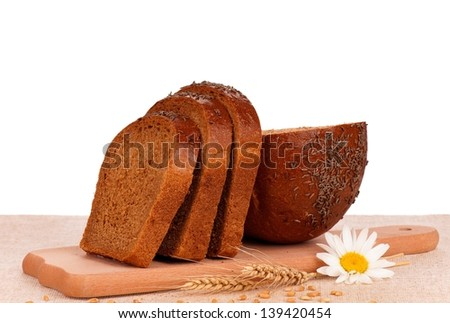 Rye bread slices on a cutting board on a burlap over white background - stock photo