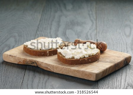 rye bread with cream cheese on wood table, rustic food - stock photo