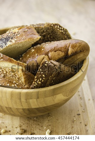 rye bread with prunes and long loaf with sesame and poppy seeds in wooden bowl