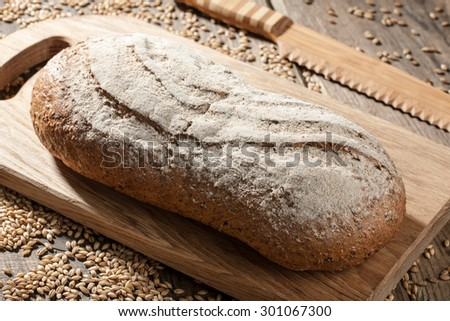 Rye bread with seeds on a cutting board on wooden table