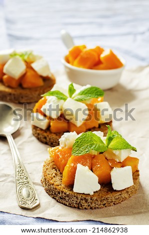 rye bruschetta with honey pumpkin and goat cheese on a blue background. tinting. selective focus on mint - stock photo