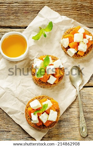 rye bruschetta with honey pumpkin and goat cheese on a dark wood background. tinting. selective focus on mint on the middle bruschetta - stock photo