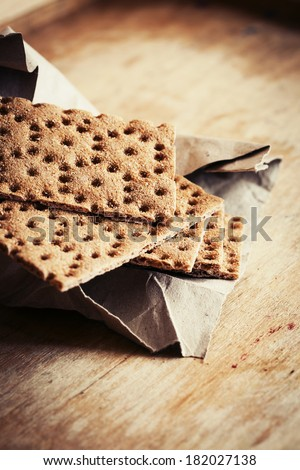 Rye crispbread bread with texture paper on wooden background / healthy eating background - stock photo