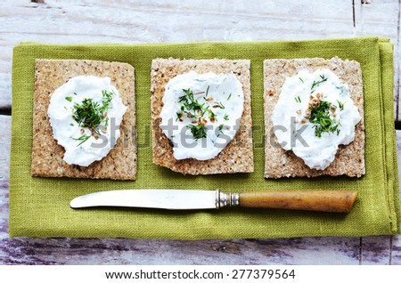Rye loaves sandwich with homemade cottage cheese spread with coriander and chopped dill on green table napkin - stock photo