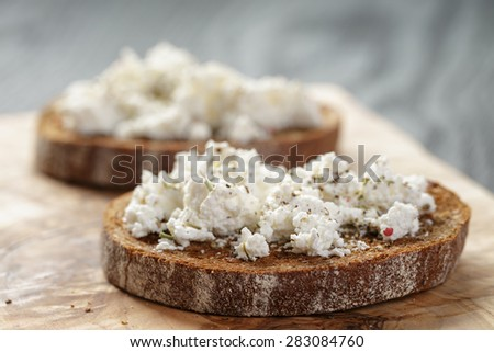 rye sandwich or bruschetta with ricotta cheese and herbs on wooden table - stock photo
