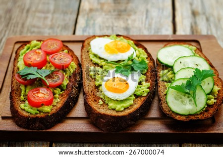rye sandwiches and mashed avocado, eggs, tomatoes and cucumbers. tinting. selective focus - stock photo