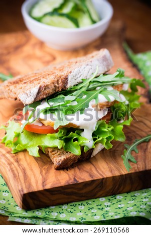Rye toast sandwich with green leaf, tomato and chicken, selective focus - stock photo