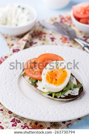 Rye toast sandwiches with egg, tomato and soft cheese, selective focus - stock photo