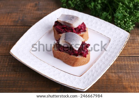 Rye toasts with herring and beets on plate on wooden background - stock photo