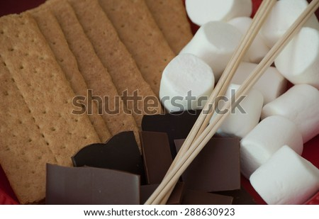 S'more ingredients: chocolate, marshmallow, graham cracker, and sticks.