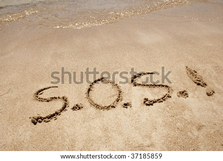 S.O.S. handwritten in sand on a beach