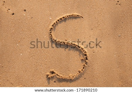 S text written in the sandy on the beach - stock photo