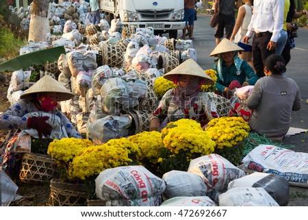 Sa Dec, Dong Thap province, Vietnam - February 07, 2015: Farmers in Vietnamese conical hat are preparing covered daisy flower pots for trading in the spring fair, the days before Tet holiday