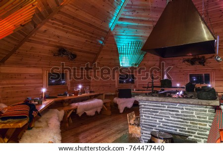 "Saariselka, Finland - November 29, 2010: In a Sami ""kota"" used to host a dinner event for tourists. The kota (also goahti), is a Sami hut or tent with a fireplace in the center."