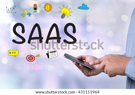 SAAS person holding a smartphone on blurred cityscape background - stock photo