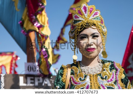 Sabah,Malaysia-April 23, 2016:Bajau lady pose for camera on traditional boat called Lepa decorated with colorfull sail known as Sambulayang during the Regatta Lepa Festival in Semporna.