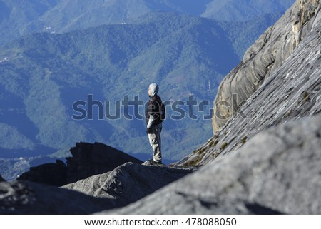 SABAH, MALAYSIA - AUGUST 23, 2014 : Climbers relax while taking a breath after reaching the Low's Peak (4095m) summit of Mount Kinabalu, Sabah, Malaysia.
