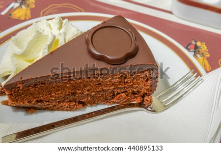 Sacher Torte with cream and fork on Plate