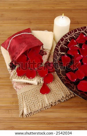 Sachet of rose petals, luxurious towels, candle and Italian glass dish filled with red rose petals