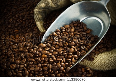 sack full of fresh coffee beans with a metal scoop - stock photo
