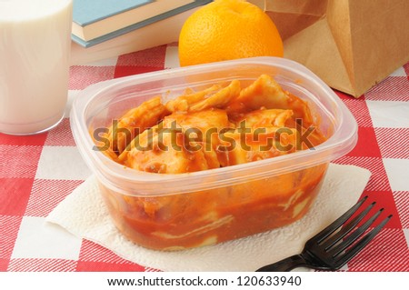 Sack lunch with leftover beef ravioli and an orange