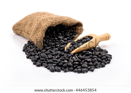 Sack of black beans spill beans with black beans in a wooden spoon on white background. - stock photo