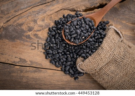 Sack of black beans spill beans with black beans in a wooden spoon on wooden table.
