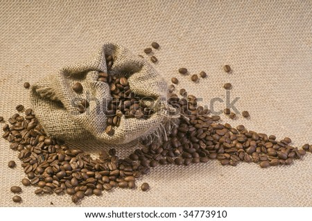 Sack of coffee beans over textured burlap background