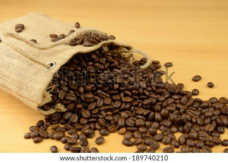 Sack of coffee beans scattered on the table - stock photo