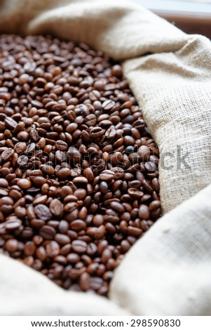 Sack of roasted coffee beans, shallow focus - stock photo