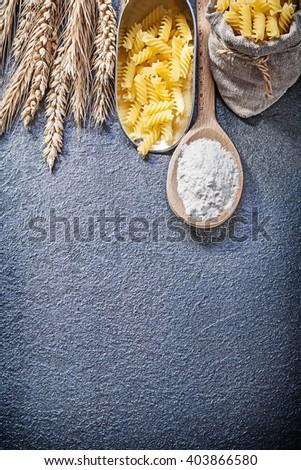 Sack short-cut macaroni serving scoop wood spoon flour ripe wheat rye ears on black background. - stock photo