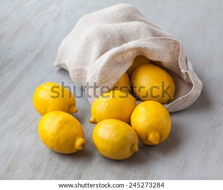 Sack with lemons on a gray wooden table - stock photo