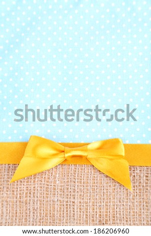 Sackcloth with color ribbon and bow on color fabric background - stock photo