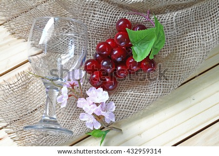 sacks and grapes and pink flower and glass  on wood background. - stock photo