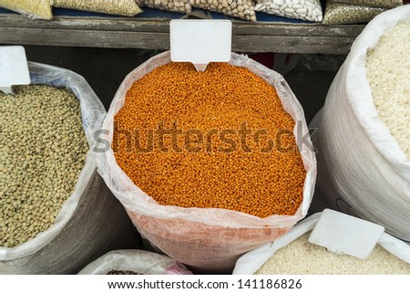 Sacks of vegetables in open market with banners