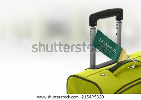 Sacramento, California. Green suitcase with label at airport. - stock photo