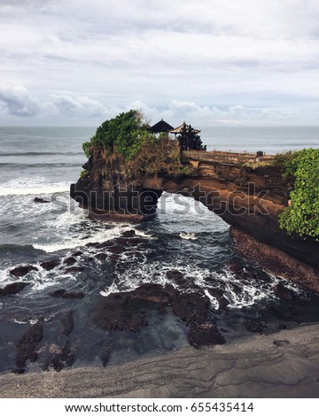 Sacred Balinese temple Tanah Lot. Pura Batu Bolong on the edge of a cliff at coastline with hole in the rock. Traditional style and architecture of Bali. Holy place for local indonesian people