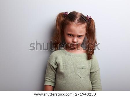 Sad abandoned kid girl looking unhappy on blue background - stock photo