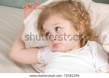 Sad adorable little girl in the bed closeup - stock photo